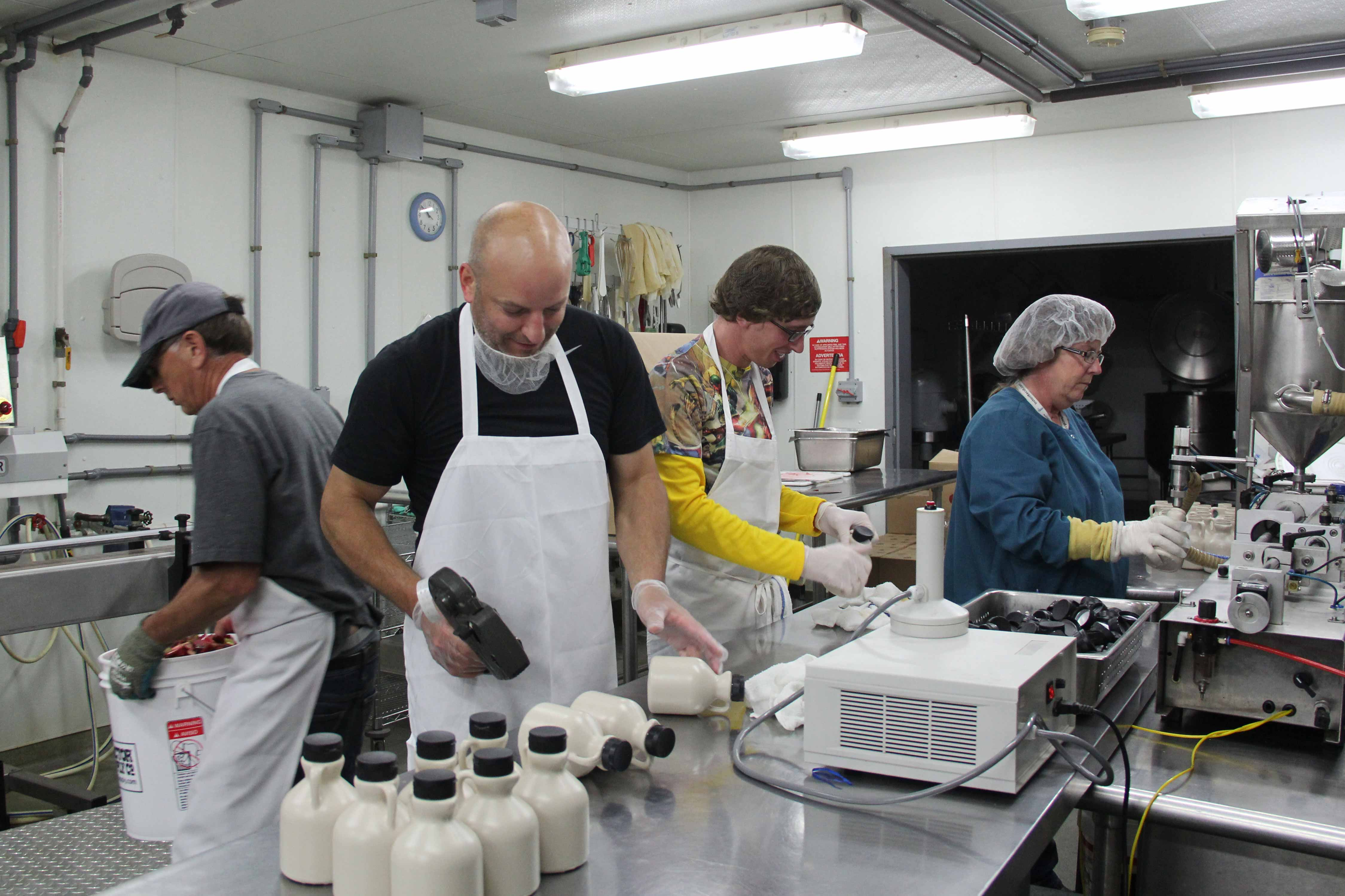 Photo of three men and one woman working together in the kitchen.